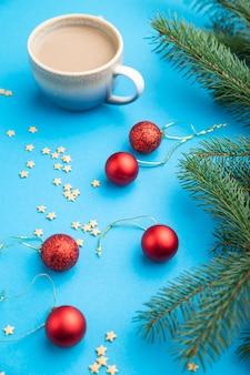 Composition de noël. décorations, boules rouges, branches de sapin et d'épinette, tasse de café sur papier bleu.