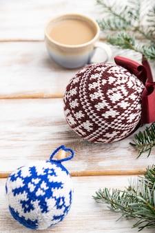 Composition de noël. décorations, boules tricotées, branches de sapin et d'épinette, tasse de café sur table en bois blanc.