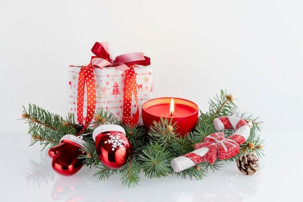 Composition de noël avec des décorations, des coffrets cadeaux, une bougie rouge, des gantelets du père noël et des boules sur blanc. vacances de noël avec fond.