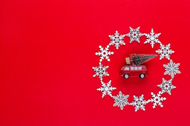 Composition de noël. décorations de guirlande de flocons de neige blanche sur fond rouge. noël, hiver, concept de nouvel an. mise à plat, vue de dessus, copie.
