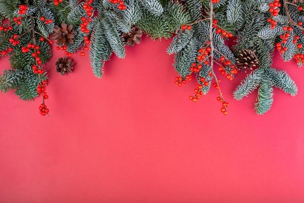 Composition de noël. décorations de noël rouge, branches de sapin avec bosses sur mur rouge. mise à plat, vue de dessus, espace copie