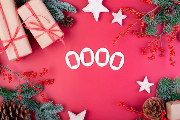 Composition de noël. décorations de noël rouge, branches de sapin avec des coffrets cadeaux jouets sur mur rouge. mise à plat, vue de dessus, espace copie