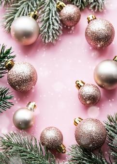 Composition de noël. décorations roses sur fond rose pastel. noël, hiver, concept de nouvel an. mise à plat, vue de dessus, espace copie