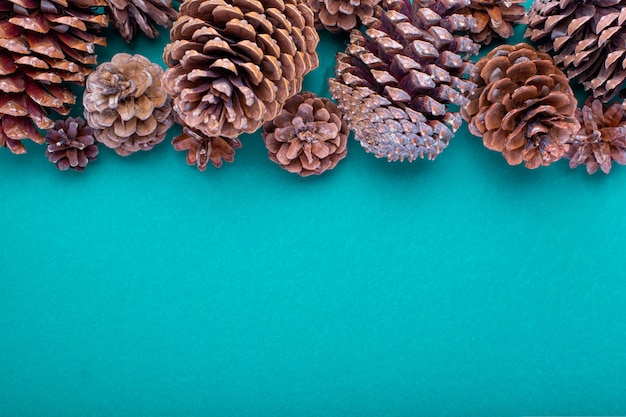 Composition de noël. décorations vertes de noël, bosses sur fond vert. mise à plat, vue de dessus, espace copie.