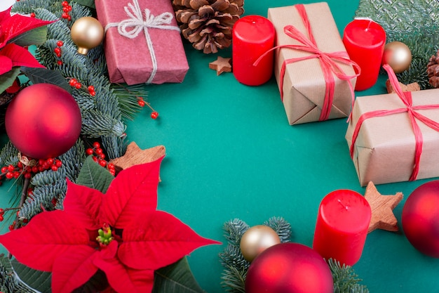 Composition de noël. décorations vertes de noël, branches de sapin avec des coffrets cadeaux jouets sur fond vert. mise à plat, vue de dessus, espace copie