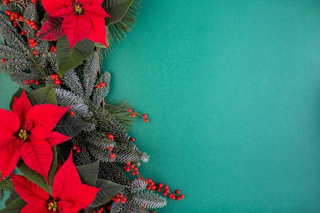 Composition de noël. décorations vertes de noël, branches de sapin avec des fleurs rouges sur le mur vert. mise à plat, vue de dessus, espace copie
