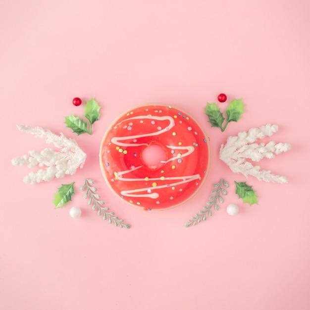 Composition de noël. donut, branches de sapin, décorations blanches sur mur rose. noël, hiver, concept de nouvel an. mise à plat minimale, vue de dessus.
