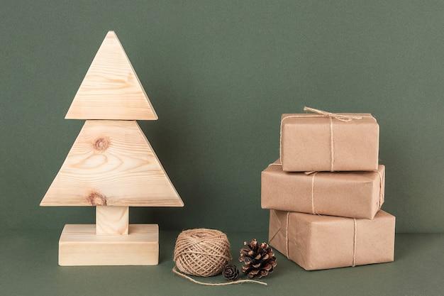 Composition de noël ou du nouvel an. arbre de noël en bois fait maison, trois cadeaux, ficelle et cône d'épinette sur fond vert. concept noël zéro déchet, respectueux de l'environnement. vue de face.
