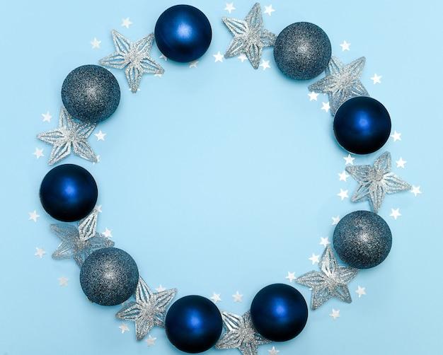 Composition de noël ou du nouvel an cadre rond fait de décoration de noël sur fond bleu