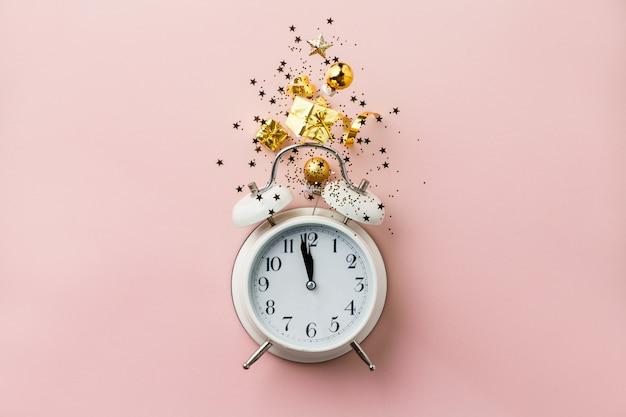 Composition de noël ou du nouvel an sur fond rose avec réveil rétro et décorations de noël
