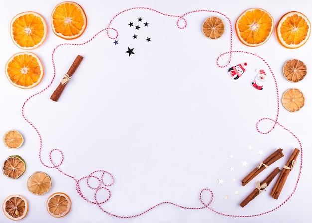 Composition de noël et du nouvel an avec des oranges séchées et citron vert, ruban et épices sur fond blanc
