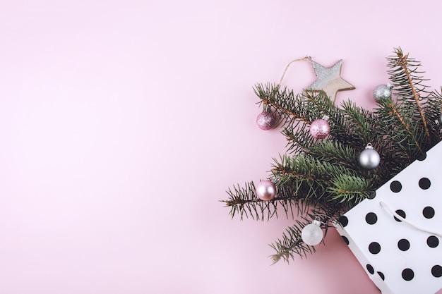 Composition de noël élégante à la mode avec sac-cadeau, branches de sapin et jouets présents sur fond pastel