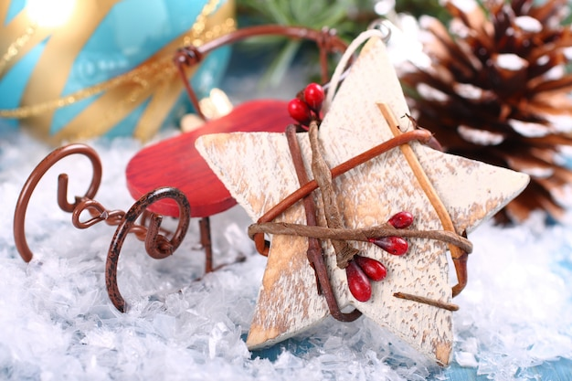 Composition de noël avec une étoile en bois et un traîneau sur la neige