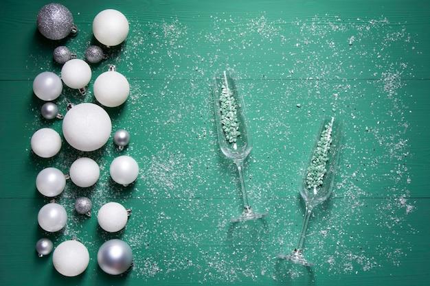 Composition de noël sur fond de bois vert avec des boules de neige et des verres de champagne vides