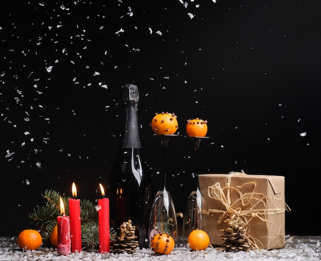 Composition de noël sur fond noir avec boîte-cadeau, mandarines, cônes de pin, bougies rouges, bouteille de champagne et deux verres empy.