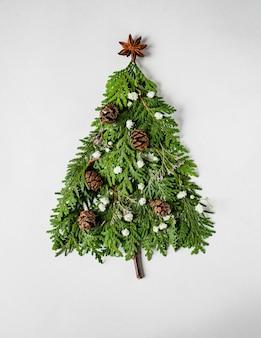 Composition de noël en forme d'arbre de noël avec des branches de thuya, des fleurs et des cônes. mise à plat