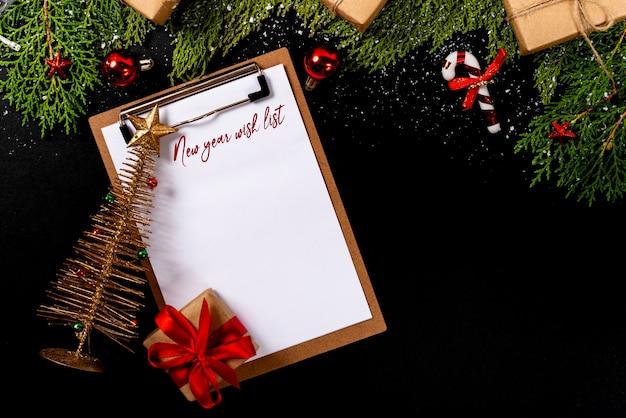 Composition de noël. girlanda avec des décorations de noël et des cadeaux sur fond noir et bloc-notes vide