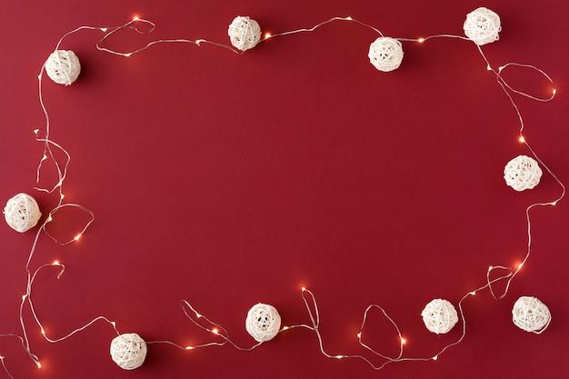 Composition de noël avec guirlande et boules blanches sur le rouge
