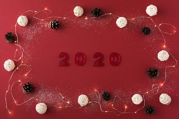 Composition de noël avec guirlande, pomme de pin, 2020 et boules blanches sur du rouge