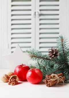 Composition de noël et d'hiver avec sapin trois branches, pomme, noix et cannelle.