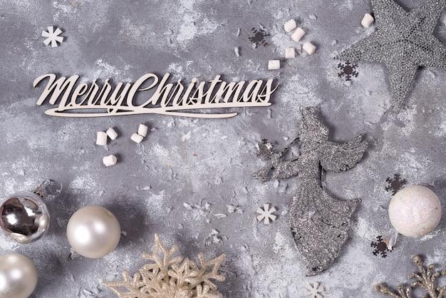 Composition de noël avec des jouets en argent du nouvel an sur fond de pierre grise