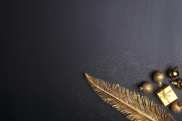 Composition de noël de jouets de noël doré et éléments de décoration sur fond noir.