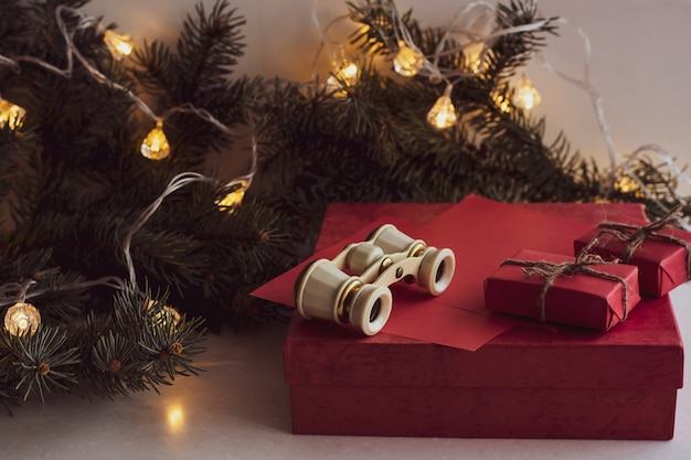 Composition de noël avec des lunettes d'opéra, une branche de sapin, des coffrets cadeaux rouges et une guirlande