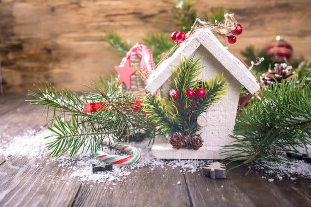 Composition de noël avec une maison en bois blanche