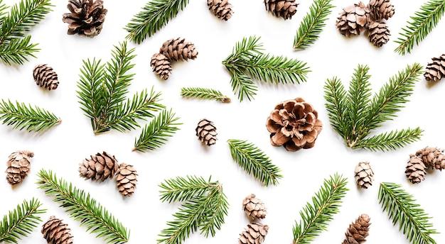 Composition de noël. motif hivernal fait de cônes et de branches de sapin sur fond blanc. vue de dessus, mise à plat
