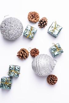 Composition de noël nouvel an. cadeaux, cônes de sapin, décorations de boule d'argent sur blanc. concept de vacances d'hiver. mise à plat, vue de dessus