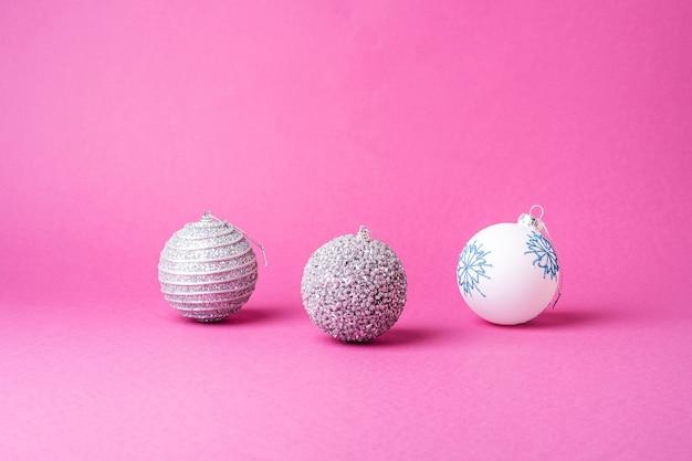 Composition de noël nouvel an. cadeaux, décorations boule argent et blanc sur fond rose. concept de vacances d'hiver. vue d'angle