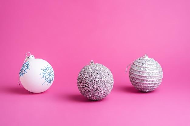 Composition de noël nouvel an. cadeaux, décorations boule argent et blanc sur rose. concept de vacances d'hiver. vue d'angle