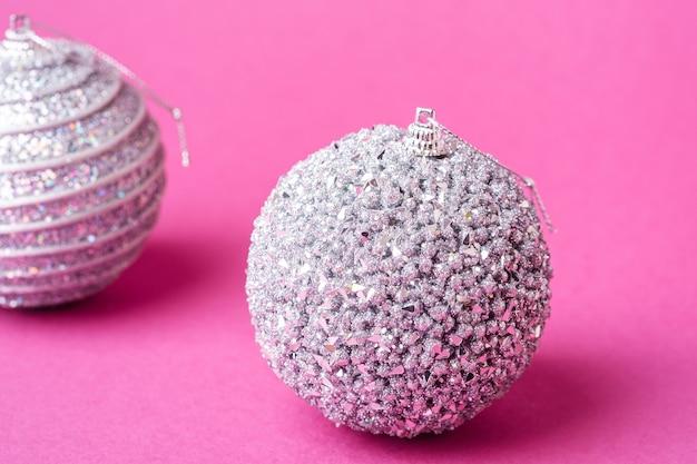 Composition de noël nouvel an. cadeaux, décorations boule argent et blanc sur surface rose. concept de vacances d'hiver. vue d'angle