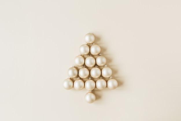 Composition de noël nouvel an. symbole de l'arbre de noël fait de boules de noël or sur beige