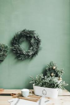 Composition de noël nouvel an. table de fête avec des branches de sapin, une tasse de café et une couronne de noël contre un mur vert pâle.