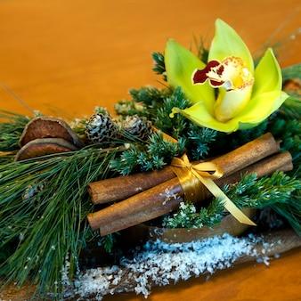 Composition de noël d'orchidée jaune, de pommes de pin, de sapin, de cannelle, de ruban d'or et de tranches de pommes séchées. avec espace copie