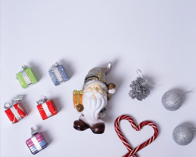 Composition de noël avec le père noël ou le gnome, cadeaux, cannes de noël en forme de coeur, boules violettes et argentées, pommes de pin sur fond blanc, mise à plat, vue de dessus, espace pour copie