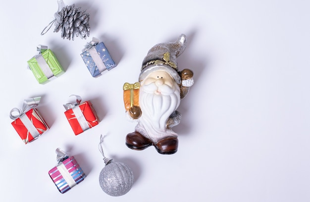 Composition de noël, père noël ou lutin, cadeaux de noël, boules d'argent et pommes de pin sur fond blanc, mise à plat, vue de dessus, espace de copie. peut être utilisé comme carte de noël