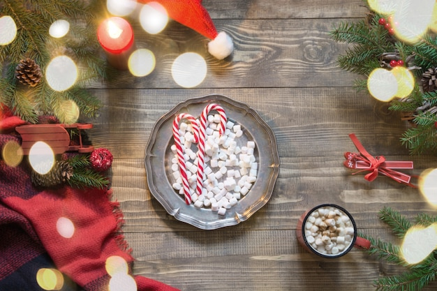 Composition de noël de plaque avec des bonbons, tasse de café, guirlande, damier pleid sur planche de bois. lay plat. vue de dessus.