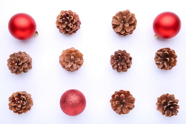 Composition de noël avec des pommes de pin et des boules de noël rouges sur fond blanc