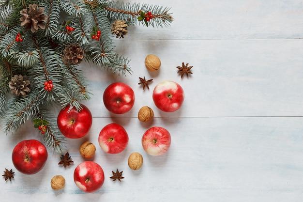 Composition de noël avec des pommes rouges, des noix, de la cannelle et d'autres ingrédients et accès