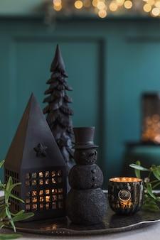 Composition de noël sur le pouf en velours vert dans le salon. belle décoration. arbres de noël, bougies, étoiles, lumières et accessoires élégants. joyeux noël et joyeuses fêtes, modèle.