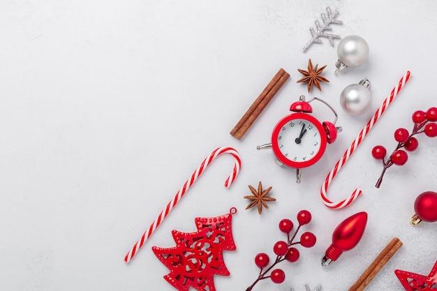 Composition de noël avec réveil, souvenirs, canne en bonbon, houx sur fond de pierre. célébration des vacances de noël 2021. mise à plat, espace de copie - image
