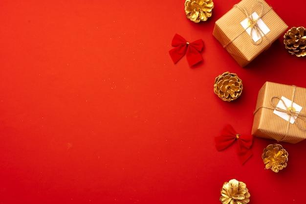 Composition de noël rouge avec des cônes d'or et des décorations vue de dessus