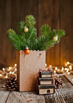 Composition de noël sac en papier avec et bosses branches de sapin brun fond en bois et des lumières de bokeh.