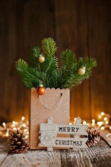 Composition de noël sac en papier avec et bosses de branches de sapin sur les lumières marron en bois et bokeh.