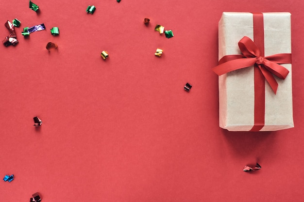 Composition de noël ou de la saint-valentin avec espace de copie. coffret avec ruban rouge et décorations de confettis sur fond coloré de papier pastel.