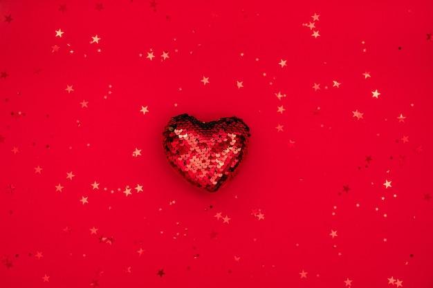 Composition de noël ou de la saint-valentin faite de décoration de coeur scintillant et de paillettes sur une surface rouge. joyeux noël et bonne année, concept happy valentine. mise à plat, vue de dessus