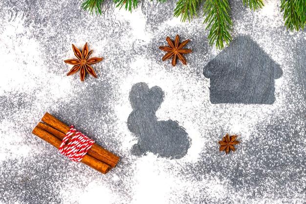 Composition de noël. silhouette de farine de cookies sur fond sombre parmi les branches d'arbres de noël, les cônes, l'anis étoilé et la cannelle.