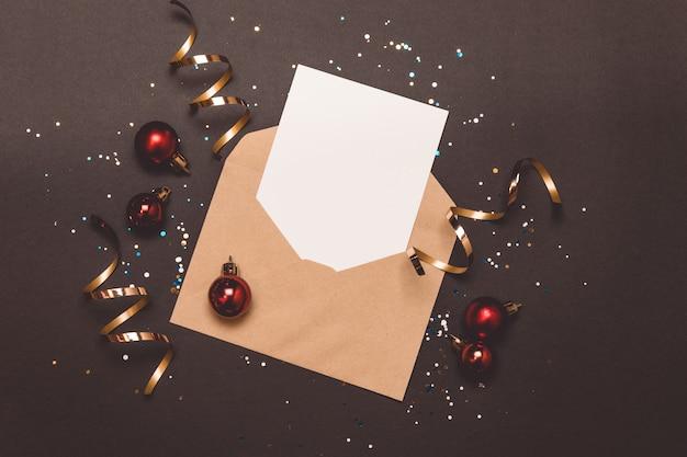 Composition de noël vacances carte vide dans une enveloppe sur fond noir.